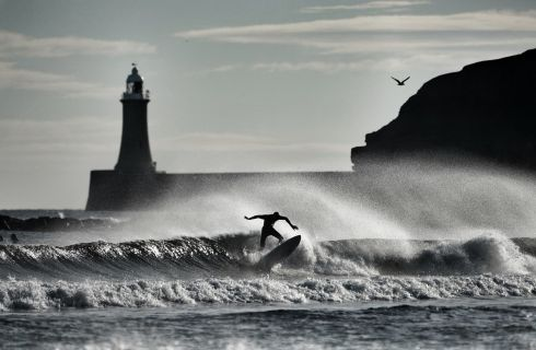 CATCHING WAVES: A surfer silhouetted against the waves at Tynemouth, near North Shields in England. Photograph: Owen Humphreys/PA Wire