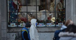 Mask-wearing people pass Christmas windows at the GPO in Dublin on Saturday. Photograph: Alan Betson