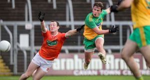 Donegal's Peadar Mogan scores a goal despite the efforts of Armagh's Ryan Kennedy of Armagh in the Ulster semi-final at Kingspan Breffni Park. Photograph: Inpho