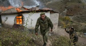 Armenian soldiers walk by a home burning near the Dadivank monastery in the Kelbajar District, before Azeris arrive to take over. Photograph: Mauricio Lima/New York Times
