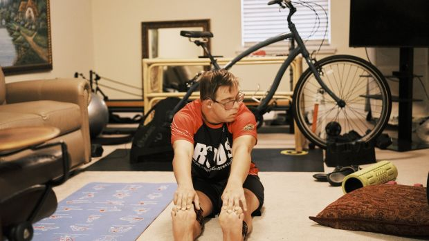 Chris Nikic stretches at his home in Maitland, Floridea. Photograph: Zack Wittman