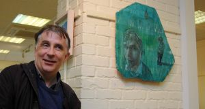 Kevin Higgins with his portrait by Christopher Banahan