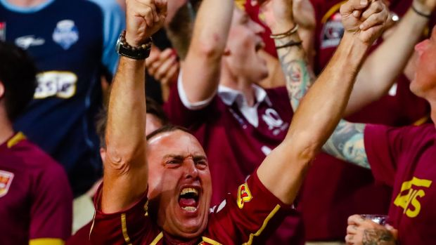 A Queensland fan celebrates during the match. Photo: Patrick Hamilton/AFP via Getty Images