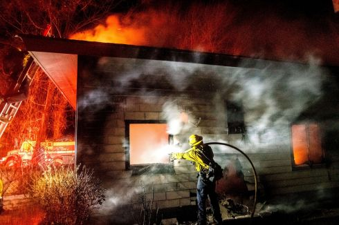 CALIFORNIA FIRE: A firefighter sprays water on a burning home as the Mountain View Fire tears through the Walker community in Mono County, California. Photograph: AP Photo/Noah Berger