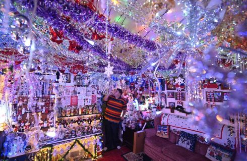 HO HO HOME: Steven Morton admires the Christmas decorations in his home as he stands in his livingroom in Hull, northern England. Photograph: Oli Scarff/AFP via Getty Images