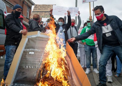 The medical staff of the CHU Brugmann in Brussels, Belgium, burn a copy of their diploma as a symbolic action in front of the hospital to denounce the royal decree which authorises a temporary period to delegate nursing acts to staff not trained to take on those duties.  Photograph: Stephanie Lecocq/Reuters