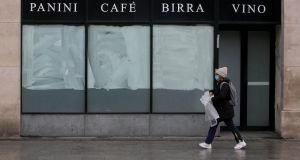 A person wearing a facemasks passes a closed Italian restaurant on O Connell Streetduring the Coronavirus Covid 19 pandemic in Dublin's city centre. Photograph: Gareth Chaney/Collins