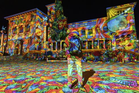 IN A DIFFERENT LIGHT: An onlooker watches a light projection entitled Diving in the Sea of Colours, by German light artist Daniel Margraf, projected onto the Palais de Rumine, Place de la Riponne, ahead of the Festival Lausanne Lumieres (Lausanne Light Festival), in Lausanne, Switzerland. Photograph: Laurent Gillieron/EPA