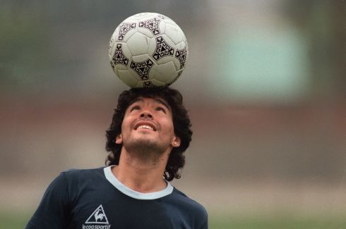 Diego Maradona juggles a ball on his head as he walks off the pitch following a training session in Mexico City in 1986. Photo: JORGE DURAN/AFP via Getty Images)