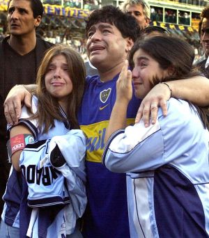 "Diego Maradona, his daughters Dalma Nerea (L) and Giannina Dinora (R) are overcome with emotion during an event in Maradona's honor at the ""La Bombonera"" stadium of Boca Juniors in 2001 in Buenos Aires. Photo: ALI BURAFI/AFP via Getty Images)"