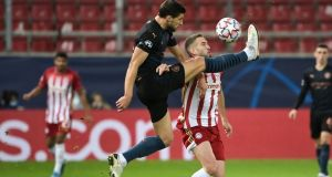 Manchester City defender Ruben Dias  fights for the ball with Olympiakos'  Kostas Fortounis during the  Champions League match at  Georgios-Karaiskakis stadium in Piraeus. Photograph: Aris Messinis/AFP via Getty Images
