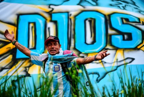 A fan in front of a banner reading God outside the Casa Rosada government house as people wait to pay their respects to Argentinian soccer legend Diego Maradona in Buenos Aires, who died on Wednesday. Photograph: Ronaldo Schemidt/Getty