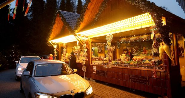 Customers sitting in their cars receiving goods at a drive-in Christmas market during the second wave of the coronavirus pandemic in Landshut, Germany. Photograph: Getty