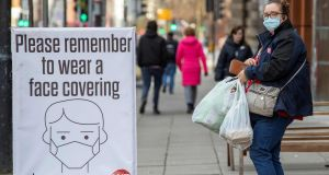 A pedestrian wearing a face covering walks past a Covid-19 information sign in Belfast on Friday. Photograph: Getty