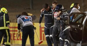 Stewards and medics attend to Romain Grosjean after the crash. Photograph:   Hamad I Mohammed/AFP via Getty Images