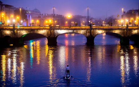 FRIDAY NIGHT LIGHTS: A man paddleboarding on the river Liffey. Photograph: Tom Honan