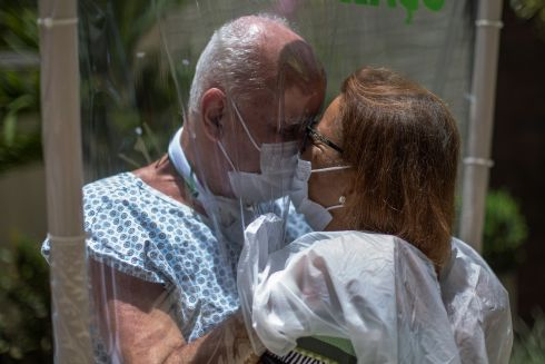 SO CLOSE YET SO FAR: Walter Candido (75) and Marlene Amaral (73), who will celebrate 50 years of marriage in a week, embrace between a plastic sheet used so that patients and relatives can hug each other, in a hospital in the city of Niteroi, Rio de Janeiro, Brazil. Photograph: Antonio Lacerda/EPA