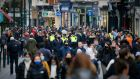 Gardai mingle with shoppers on Grafton Street as non-essential retail re-opened after the six-week lockdown. Photograph: Crispin Rodwell/The Irish Times