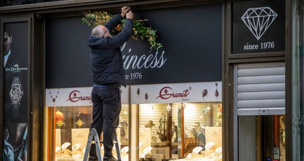 A man wearing a  face mask places Christmas decorations over a shop window during preparations for reopening in Prague, Czech Republic,  on Wednesday. Photograph: Martin Divisek/EPA