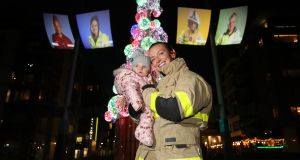 Frontline workers projected as Dublin firefighters. Nicola Sheil (Dolphins Barn) and her nine-month-old daughter Gabrielle attend the launch of Winter Lights 2020. Photograph: Nick Bradshaw/The Irish Times