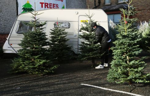 Niall McDonnell, a member of the 31st Rathfarnham Scouts Group in Dublin, makes preparations as he opens for business selling Christmas trees and wreaths to raise funds for their group, a portion of their takings is also donated to charity. Photograph: Brian Lawless/PA