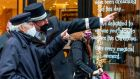 A doorman gives directions to a pedestrians wearing a face mask-due  along a busy shopping street in Dublin on Tuesday. Photograph: Paul Faith/AFP