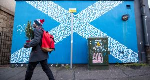 A man carrying a Christmas tree walks past a mural depicting a Saltire design in Leith, Edinburgh on St Andrew's Day. Support for independence has increased to 54 or 55 per cent. Photograph: Jane Barlow/PA