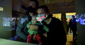 LIGHTING UP: Katie Whelan (5 months) a patient at Childrens Health Ireland (CHI) at Crumlin Hospital with parents Shane and Elaine look through a window into the St Annes Ward garden as Children's Health Foundation Crumlin ambassador Rob Kearney performs the official switching on of the Christmas lights in the hospital. Photograph: The Irish Times