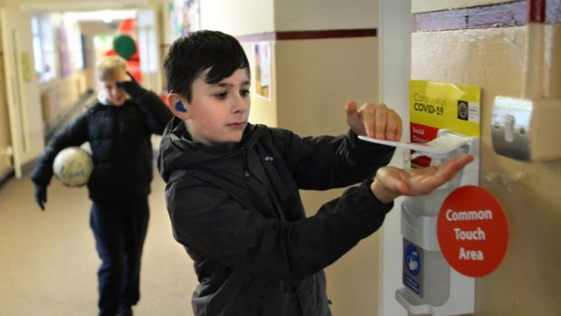 Nathan Ryan, using the hand sanitiser before entering the classroom at St Audoen's National School, Cook Street, Dublin. Photograph: Dara Mac Dónaill/The Irish Times