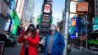 Tourists  wearing  face masks  when visiting Times Square in New York. Photograph:  Kena Betancur/AFP via Getty Images