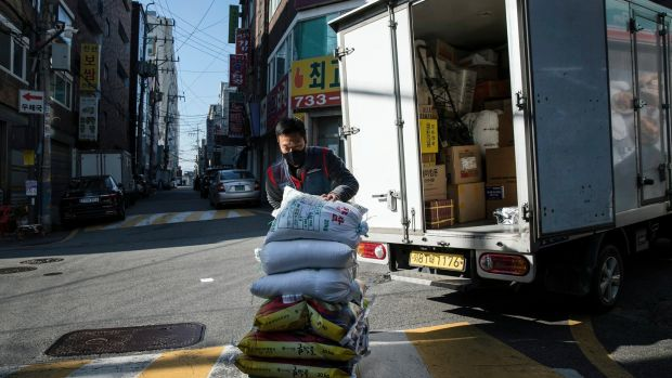 Park Ki-Ryeon delivers bags of rice to customers in Seongnam, a city on the outskirts of Seoul. Photograph: Woohae Cho/The New York Times