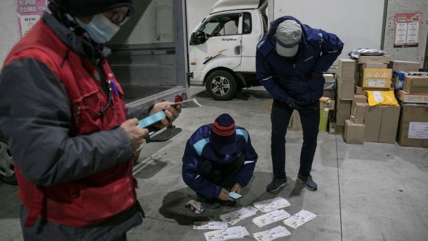 Couriers check delivery addresses at a distribution centre in Seoul. Photograph: Woohae Cho/The New York Times