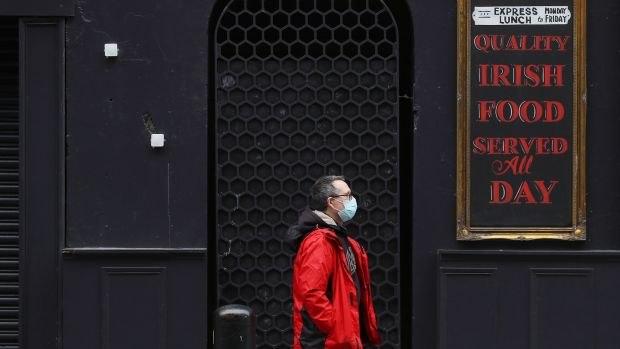A man passes a closed pub in Dublin's city centre The Government is to consider on Tuesday new advice from the National Public Health Emergency Team (Nphet) regarding new restrictions on hospitality and household visits. Photograph: PA