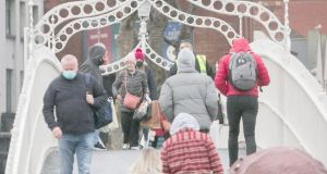 Masked Christmas shoppers are seen on the Ha'penny Bridge last week in Dublin city centre. Photograph: Collins