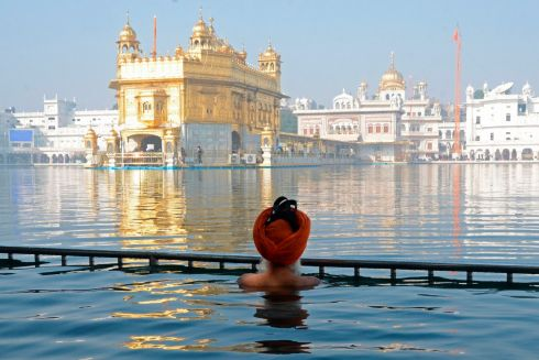 A Sikh devotee takes a dip in the holy sarovar (water tank) of the Golden Temple on the Martyrdom Day of the ninth Sikh Guru Tegh Bahadur in Amritsar. Photograph: Narinder Nanu/Getty