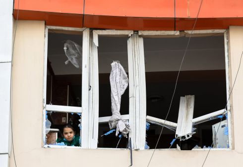 An Afghan girl looks out from the damaged window of her apartment, which faces the scene of a bomb explosion, in Kabul, Afghanistan. At least nine people were killed and many others injured after an explosion targeted the vehicle of Haji Khan Mohammad Wardak, a member of parliament from Kabul, according to local reports. Wardak survived the attack.  Photograph: Hedayatullah Amid/EPA