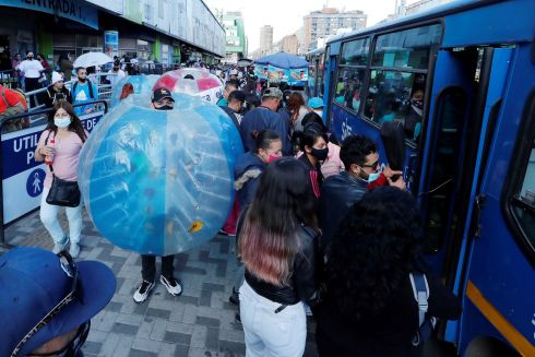 Workers at the El Gran San Shopping Center walk inside balloons as part of a campaign to maintain physical distance between shoppers during the Christmas season, in Bogota, Colombia. Photograph: EPA