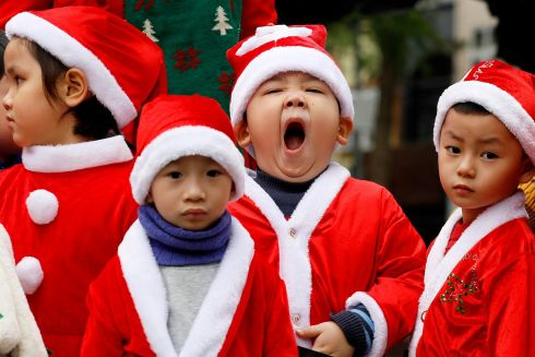 LITTLE HELPERS: Children in Santa Claus outfits visit a church in Hanoi, Vietnam. Christmas is not an official holiday in Vietnam, but there is a significant minority Christian population in the country. Photograph: Luong Thai Linh/EPA