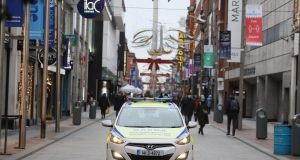 A Garda car on Henry Street in Dublin city centre, where retailers have been asked to defer sales until January.  Photograph: Brian Lawless/PA Wire