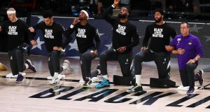 LA Lakers players including LeBron James (third from right) kneel during the national anthem. Photo: Michael Reaves/Getty Images