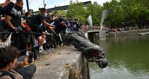 Protesters throw a statue of slaver Edward Colston into Bristol harbour during a Black Lives Matter protest rally in June 2020. Photograph: Ben Birchall/PA Wire