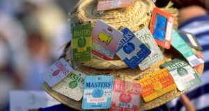 A masters fans displays the past entry tickets of the Masters on his hat. Photo: Craig Jones /Allsport