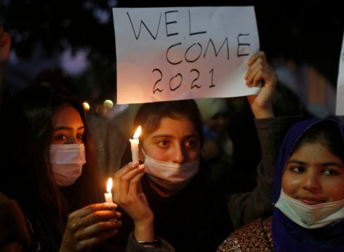 People hold candles and participating in a demonstration to welcome new year, in Lahore, Pakistan. Photograph : K.M. Chaudary / AP