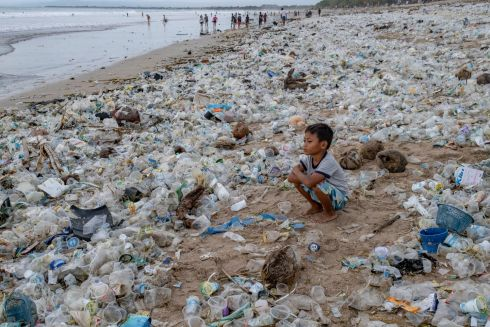 A boy sits on beach covered in plastic wastes at Kuta Beach in Bali, Indonesia. Photograph: Made Nagi /  EPA