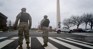 Members of the New York Army National Guard prepare to close a road near the White House in Washington, DC on Tuesday. The city's mayor, Muriel Bowser, urged residents not to engage with any protesters 'seeking confrontation'.  Photograph: Erin Scott/Bloomberg