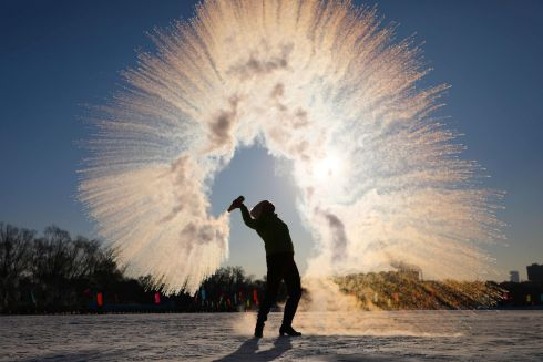 FREEZING: A woman throws hot water into the air, which instantly condenses into ice crystals amid temperatures of minus 27 degrees, in Shenyang, China. Photograph: STR/AFP/China Out via Getty Images