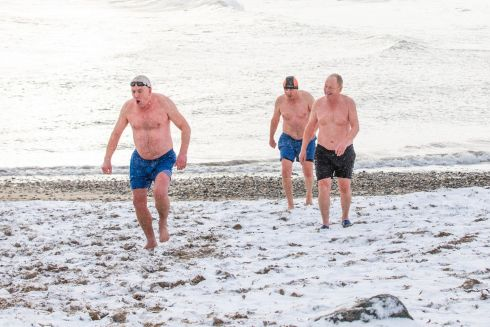 COLD DIP: Swimmers (from left) Jim Curran, Liam Walsh and Lorcan Byrne brave the cold conditions at a snow-covered beach at Bray seafront. Photograph: Naoise Culhane