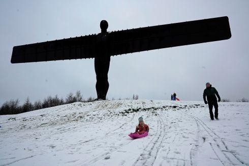 ANGEL IN SNOW: Sledgers have fun in the snow surrounding the Angel of the North near Gateshead, Tyne and Wear. Photograph: Owen Humphreys/PA Wire