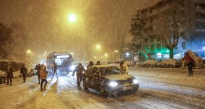 People push a car stranded in the snow in Madrid, Spain. Photograph:  EPA/Rodrigo Jimenez