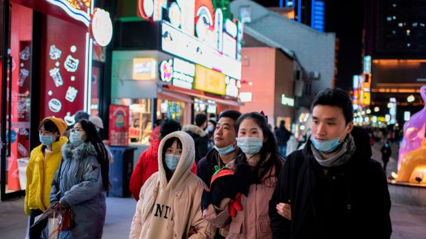 People walk on Jianghan street in Wuhan on Sunday, the eve of the first anniversary of China confirming its first death from the Covid-19 coronavirus. Photograph: Nicolas Asfouri/AFP via Getty Images